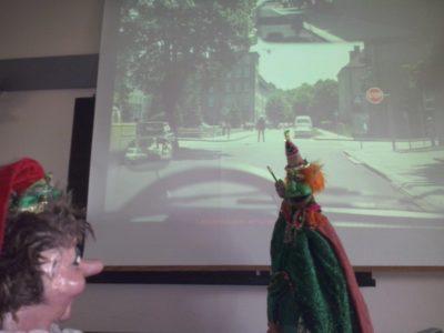 Tintifax erörtert dem staunenden Kasperl die Verkehrslage auf dem Banner..