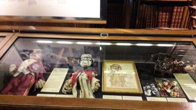 """Theater Arlequin Wien: Vitrine im Prunksaal mit unseren Exponaten, Portraitpuppen von H. Zilk und O. Bronner, Original-Zeichnung """"Kasperl"""" von Arminio Rothstein."""